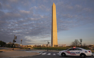 A District of Columbia Police Car blocks the road near the Washington Monument in an effort to discourage crowds from visiting the cherry blossom trees in full bloom, Sunday, March 22, 2020, in Washington. Sections of the National Mall and tidal basin areas have been closed to vehicular traffic to encourage people to practice social distancing and not visit Washington's iconic cherry blossoms this year due to coronavirus concerns. The trees are in full bloom this week and would traditionally draw a large crowd. (AP Photo/Jacquelyn Martin)