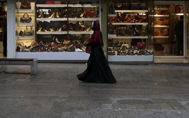 A woman wearing a face mask as a preventive measure against the spread of the new coronavirus walks past shoe shops in a mostly empty street in a commercial district in downtown Tehran, Iran, March 22, 2020. (Vahid Salemi/AP)