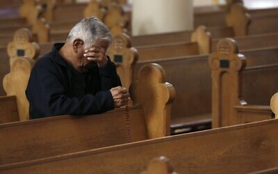 A parishioner wipes away tears during a modest and shortened service due to the coronavirus, at St. Mary's Roman Catholic Basilica in Phoenix, Arizona, March 22, 2020. (Ross D. Franklin/AP)