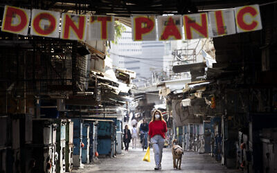 """A woman walks her dog under a """"don't panic"""" sign hanging on the entrance of the shuttered Carmel Market in Tel Aviv, March 23, 2020. (AP/Oded Balilty)"""