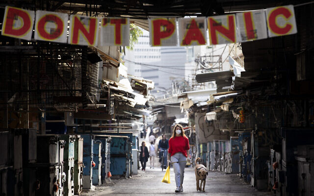 "A woman walks her dog under a ""don't panic"" sign hanging on the entrance of the shuttered Carmel Market in Tel Aviv, March 23, 2020. (AP/Oded Balilty)"