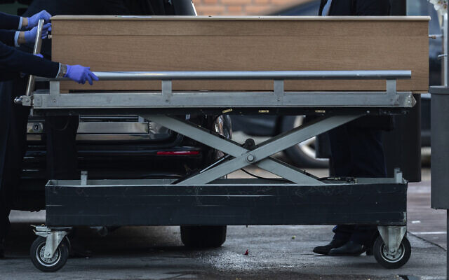 Undertakers carry a coffin of a person who died of COVID-19 at the La Almudena cemetery in Madrid, Spain, March 23, 2020. (Bernat Armangue/AP)