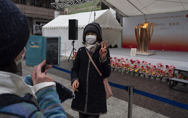 A woman poses for a photo with the Olympic Flame during a ceremony in Fukushima City, Japan, March 24, 2020 (AP Photo/Jae C. Hong)