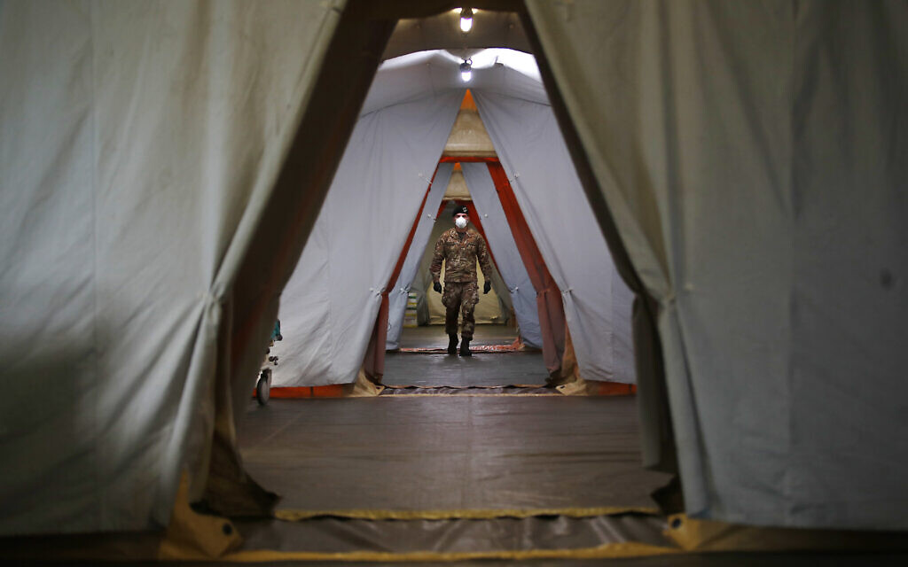 An Italian soldier walks inside the field hospital built in Crema, Italy, Tuesday, March 24, 2020. (AP Photo/Antonio Calanni)