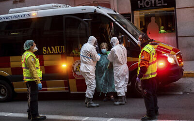 A patient is transferred to a hotel converted into a facility for coronavirus amid an outbreak in Madrid, Spain, March 24, 2020. (AP Photo/Bernat Armangue)