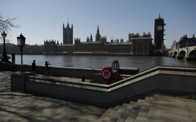 A general view of the Houses of Parliament seen from the south bank of the River Thanes in London, Wednesday, March 25, 2020. (AP Photo/Matt Dunham)