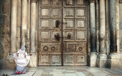 A woman prays in front of the closed Church of the Holy Sepulchre, in the Old City of Jerusalem, March 25, 2020. (Mahmoud Illean/AP)