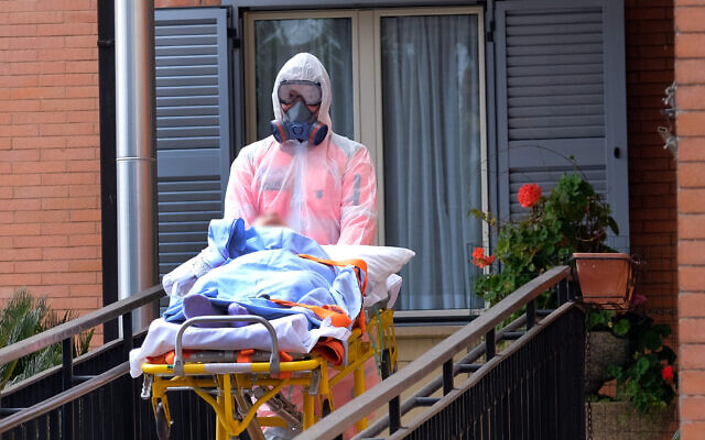 A resident of the Giovanni XIII retirement home  affected by coronavirus is evacuated to hospital, in Rome, March 25, 2020.  (Mauro Scrobogna/LaPresse via AP)