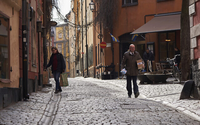 People walk down a quiet cobbled street in Stockholm, March 25, 2020. (AP Photo/David Keyton)