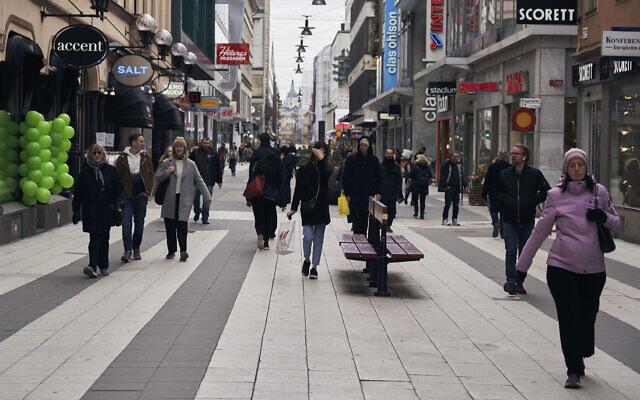 People walk along the main pedestrian shopping street in Stockholm, March 25, 2020. (AP Photo/David Keyton)