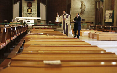Don Marcello Crotti, left, blesses the coffins with Don Mario Carminati in the San Giuseppe church in Seriate, Italy, March 28, 2020  (AP Photo/Antonio Calanni)