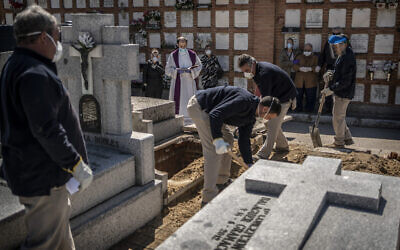 A priest and relatives pray as a victim of the COVID-19 is buried by undertakers at the Almudena cemetery in Madrid, Spain, March 28, 2020 (AP Photo/Olmo Calvo)