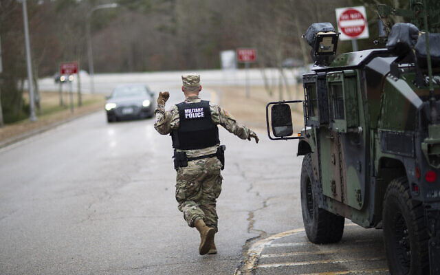 A member of the Rhode Island National Guard Military Police directs a motorist with New York license plates at a checkpoint on I-95 near the border with Connecticut where New Yorkers must pull over and provide contact information and are told to self-quarantine for two weeks, Saturday, March 28, 2020, in Hope Valley, R.I. (AP/David Goldman)