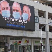 A billboard shows Israeli Prime Minister Benjamin Netanyahu, left, Avigdor Liberman, center, and Blue and White party leader Benny Gantz, wearing masks in the Israeli city of Ramat Gan on March 29, 2020. (AP/Sebastian Scheiner)