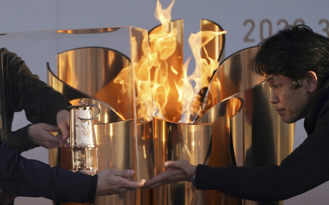 In this March 25, 2020, file, photo, officials light a lantern from the Olympic Flame at the end of a flame display ceremony in Iwaki, northern Japan. (AP/Eugene Hoshiko)