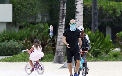 A man wears a mask as he walks along Waikiki Beach in Honolulu on Saturday, March 28, 2020. (AP/Caleb Jones)