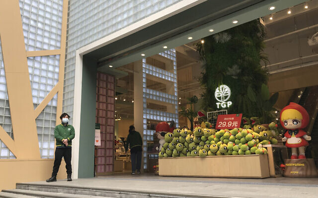 A store employee waits outside for customers at a re-opened retail street in Wuhan in central China's Hubei province on March 30, 2020. (AP Photo/Olivia Zhang)
