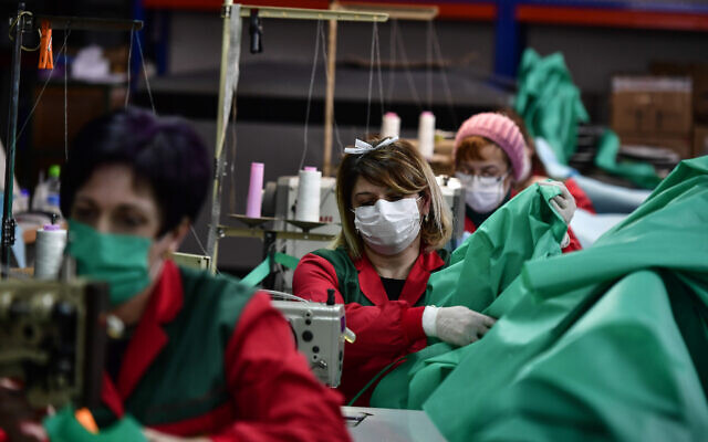 Volunteer workers in a clothing factory manufacturing firefighting gear, make hospital gowns for medical staff to protect them from the coronavirus, in Arnedo, northern Spain, March 30, 2020. (AP Photo/Alvaro Barrientos)