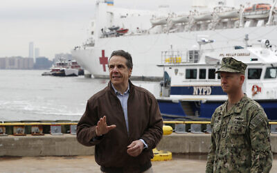 New York Governor Andrew Cuomo, left, gestures during a brief news conference as he stands beside Rear Adm. John B. Mustin as the USNS Comfort, a naval hospital ship with a 1,000 bed-capacity, pulls into Pier 90, March 30, 2020, in New York. (AP/Kathy Willens)