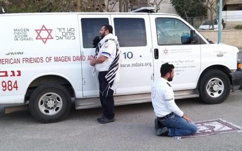 This handout photo provided by the Magen David Adom (MDA) national emergency service on March 24, 2020, in Beersheba shows two paramedics praying outside an ambulance of the American Friends of Magen David Adom (AFMDA): a Jew from Beersheba facing Jerusalem, and an Arab from Rahat facing Mecca. (Magen David Adom)