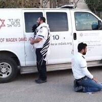 A Jewish (L) and Muslim paramedic praying side by side next to an ambulance in Beersheba. (Magen David Adom)