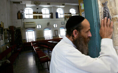 Illustrative: An ultra-Orthodox Jewish man kisses the mezuzah as he exits a synagogue in Jerusalem, August 5 2008. (Olivier Fitoussi /FLASH90)