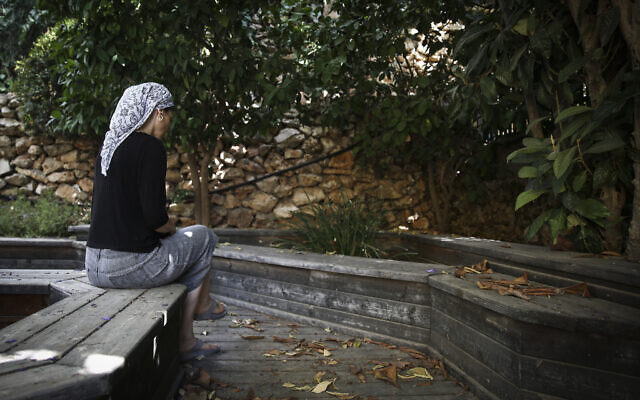 Illustrative photo: An Orthodox Jewish woman sits in the garden of the abused women's shelter in Beit Shemesh, July 15, 2014. (Hadas Parush/Flash90)
