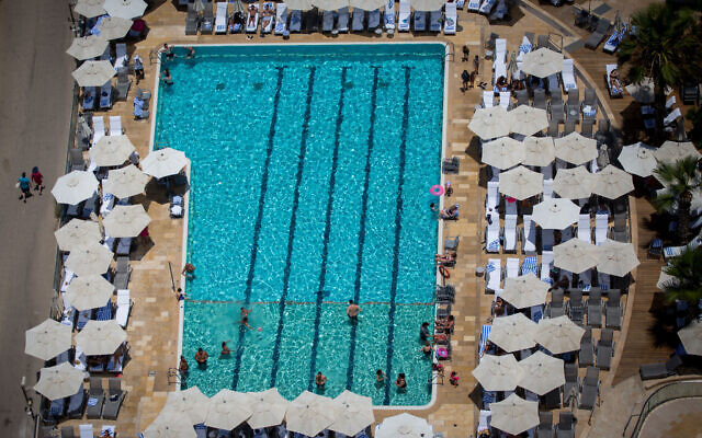 Tourists swim in a hotel pool in Tel Aviv,  on a warm summer day on July 04, 2017. (Miriam Alster/FLASH90)