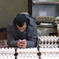 Illustrative: A salesman on his phone while selling eggs at an eggs tand in Jerusalem's Machane Yehuda Market, January 27, 2018.