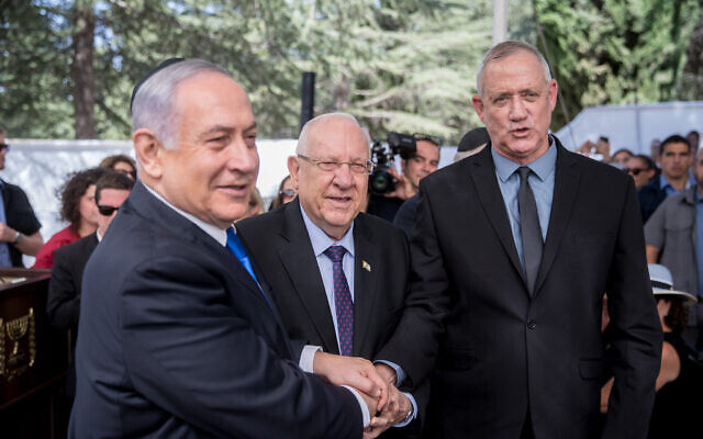 President Reuven Rivlin, center, Prime Minister Benjamin Netanyahu, left, and Blue and White leader Benny Gantz shake hands at the memorial ceremony for the late president Shimon Peres at the Mount Herzl cemetery in Jerusalem on September 19, 2019. (Yonatan Sindel/Flash90)