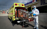 A Magen David Adom ambulance service worker wears protective clothing as a preventive measure against the coronavirus seen outside the special emergency call center in Kiryat Ono on February 26, 2020. (Flash90)