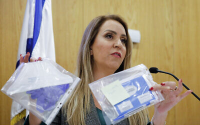 Central Elections Committee head Orly Adas shows a mock quarantined vote, during a press conference at the Knesset in Jerusalem on February 26, 2020. (Olivier Fitoussi/Flash90)