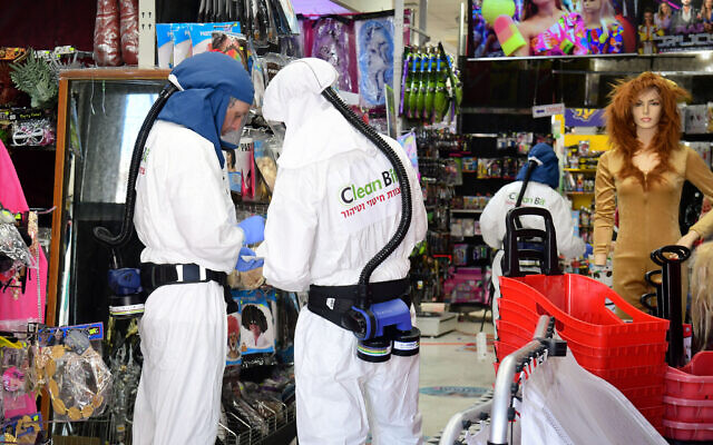 Workers disinfect a shop in Or Yehuda, after a man who works at the shop and returned from Italy tested positive for coronavirus, February 28, 2020. (Flash90)