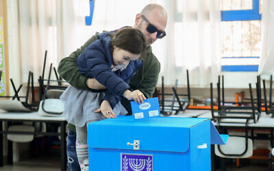 A voter and his daughter cast a ballot at a voting station in Tel Aviv, March 2, 2020 (Flash90)