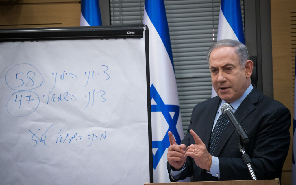 """Prime Minister Benjamin Netanyahu addresses a meeting with members of the right-wing and Orthodox parties. On the board, he writes that the Zionist right has won 58 seats in the elections, and the Zionist left 47 -- comprising Blue and White, Yisrael Beytenu and Labor-Gesher-Meretz. (Crossed out is """"Left-wing camp - 54.) These figures exclude the Joint List of mainly Arab parties, which won 15 seats in the March 2 election (Yonatan Sindel/Flash90)"""