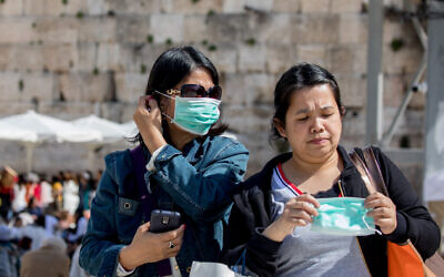 Tourists wearing face masks for fear of the coronavirus tours at the Western Wall in the Old City of Jerusalem on March 5, 2020. (Olivier Fitoussi/Flash90)