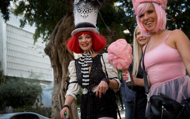 Israelis dressed up in costumes, as is customary during the Jewish holiday of Purim, seen on Rothschild Boulevard in Tel Aviv, on March 07, 2020. (Miriam Alster/Flash90)
