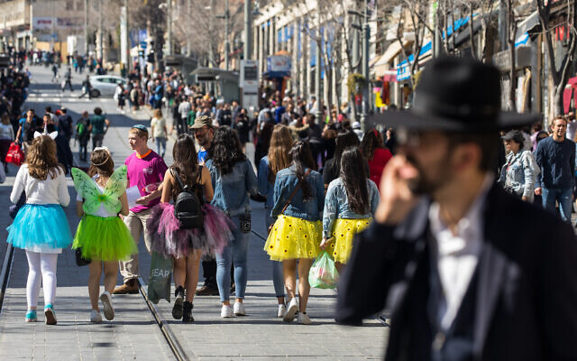 Israeli teenagers dressed up in costumes ahead the jewish holiday of Purim walk in the city center of Jerusalem on March 8, 2020. (Olivier Fitoussi/Flash90)
