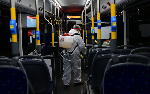 Workers wearing protective suits disinfect a bus as a preventive measure amid fears over the spread of the coronavirus, in Tel Aviv on March 9, 2020. (Tomer Neuberg/Flash90)