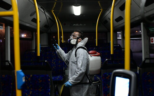 Workers wearing protective suits disinfect a bus as a preventive measure amid fears over the spread of the coronavirus, in Tel Aviv on March 9, 2020, . (Tomer Neuberg/Flash90)