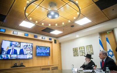 Prime Minister Benjamin Netanyahu, right, and Health Minister Yaakov Litzman hold a video conference with European leaders at the Foreign Ministry in Jerusalem, on March 9, 2020. (Yonatan Sindel/Flash90)