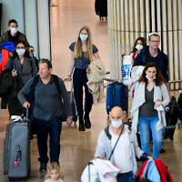 People wearing face masks for fear of the coronavirus arrive at Ben Gurion International Airport on March 10, 2020 (Avshalom Sassoni/Flash90)