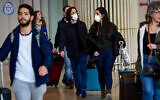 Illustrative: People wearing face masks at the Ben Gurion International Airport on March 10, 2020. (Avshalom Sassoni/ Flash90)