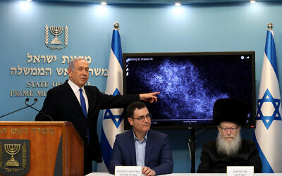 Prime Minister Benjamin Netanyahu, left,  with Health Ministry director-general Moshe Bar Siman Tov, center, and Health minister Yaakov Litzman at a press conference about the coronavirus COVID-19, at the Prime Ministers office in Jerusalem on March 11, 2020. (Flash90)