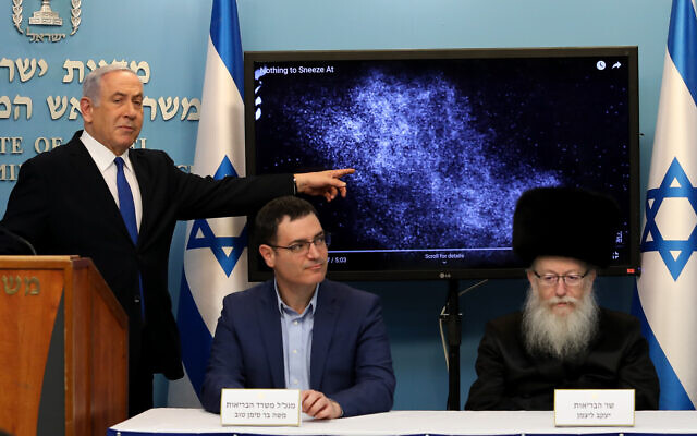 Prime Minister Benjamin Netanyahu with Health Minister Yaakov Litzman (right) and Health Ministry Director General Moshe Bar Siman-Tov at a press conference about the coronavirus COVID-19, at the Prime Minister's Office in Jerusalem on March 11, 2020. Netanyahu is explaining how the coronavirus can spread from a sneeze. (Flash90)