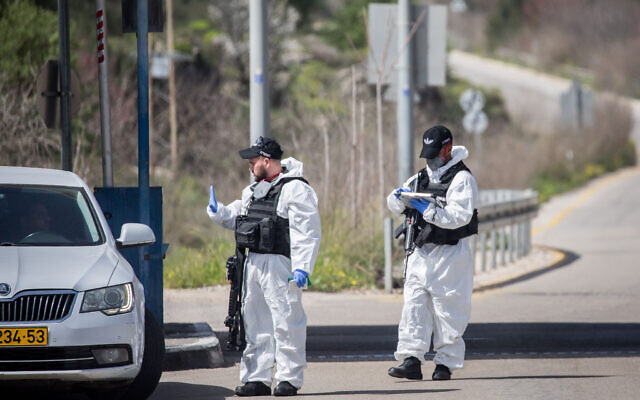 Israeli border police wear protective gear and masks at the Ein Yael Checkpoint, near the Jerusalem Biblical Zoo, March 11, 2020. (Yonatan Sindel/Flash90 )