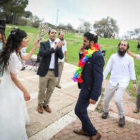 Illustrative: Hananel Even Hen and Shiran Habush celebrate during thier wedding at a public park in the Jewish Settlement of Efrat, in Gush Etzion, March 15, 2020, after their wedding was cancelled due to new regulations following the spread of the coronavirus. (Gershon Elinson/Flash90)