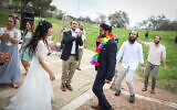 Hananel Even Hen and Shiran Habush celebrate during thier wedding at a public park in Efrat, in Gush Etzion, March 15, 2020, after their wedding was canceled due to new regulations following the spread of the coronavirus (Gershon Elinson/Flash90)