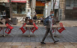 Man wearing a mask walks past closed a cafe in Jerusalem on March 15, 2020 (Nati Shohat/Flash90)