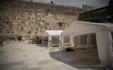 People pray in enclosed areas allowing prayers of 10 people in a time, at the Western Wall, in the Old City of Jerusalem, March 15, 2020. (Yonatan Sindel/Flash90)